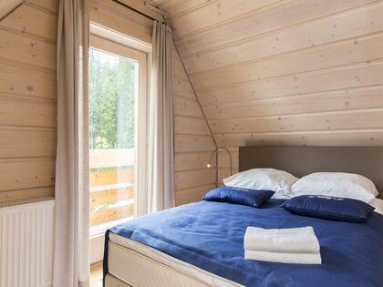 apartment 1050 West 2 Kościelisko 1 zamykana sypialnia z łóżkiem małżeńskim oraz wyjście na balkon.