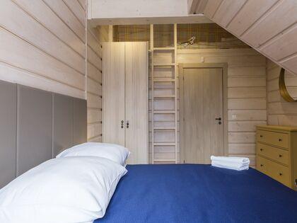 apartament 1050 West 2 Kościelisko 3 zamykana sypialnia z łóżkiem małżeńskim oraz wysoką antresolą.